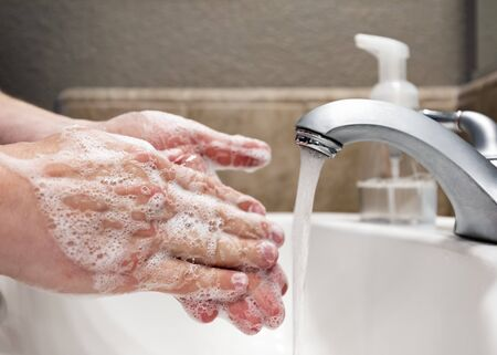 Washing hands with soap and water in bathroom sink, protection against covid-19 coronavirus flu viruses Reklamní fotografie - 145038475
