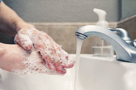 Washing hands with soap and water in bathroom sink, protection against covid-19 coronavirus flu viruses