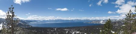 Lake Tahoe panorama with snow on the ground and view on peaks of Sierra Nevada mountains