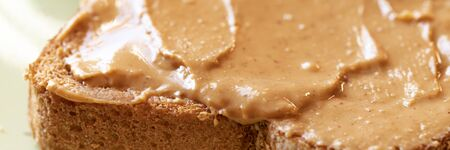 Creamy peanut butter spread on healthy whole wheat toast bread