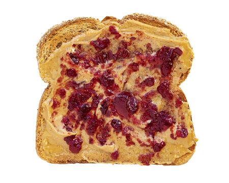 Creamy peanut butter spread with fruit jam on healthy whole wheat toast bread, isolated on white background, photographed from above