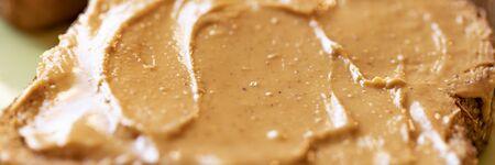Creamy peanut butter spread on healthy whole wheat toast bread