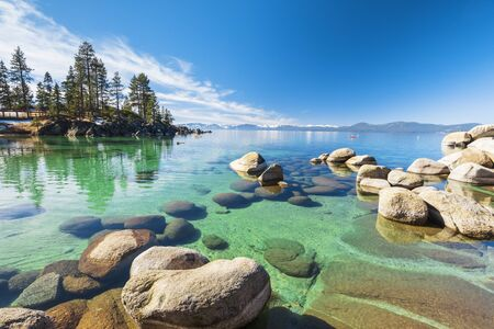 Lake Tahoe rocky shoreline in sunny day, beach with blue sky over clear transparent water Reklamní fotografie