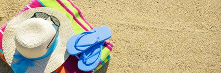 Beach towel with hat, sunglasses and flip flops photographed from above on sandy beach, hot summer day accessories, vacation destination