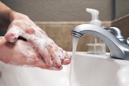Washing hands with soap and water in bathroom sink, protection against viruses and bacteria, hygiene to stay healthy