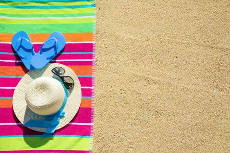 Beach towel with hat, sunglasses and flip flops photographed from above on sandy beach, hot summer day accessories, vacation destination, sunny tropical beach background Reklamní fotografie