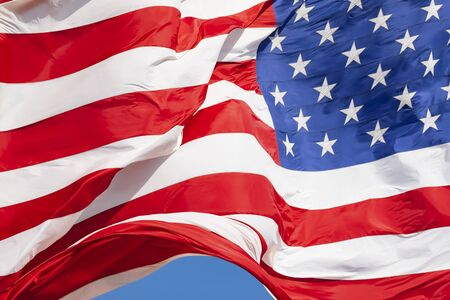 American flag waving in the wind on blue sky, US flag motion close-up, red white blue flag outdoors in sunlight. United States of America national flag. USA stars and stripes Reklamní fotografie
