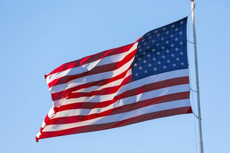 American flag waving in the wind on blue sky Reklamní fotografie - 147559609