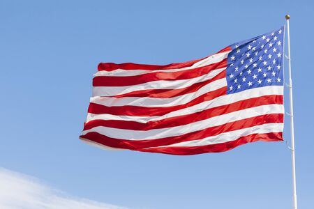 American flag waving in the wind on blue sky Reklamní fotografie - 147559610