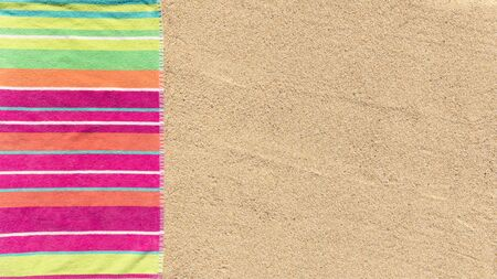 Beach towel photographed from above on sandy beach with copy space