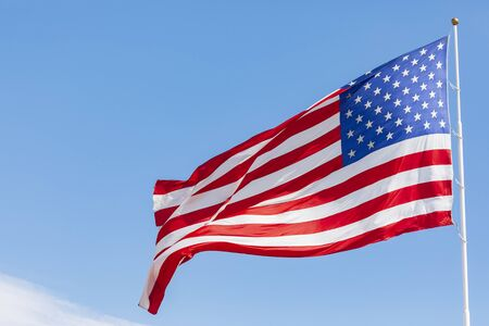 American flag waving in the wind, US flag motion on blue sky, United States of America national flag. USA stars and stripes