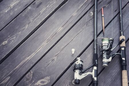 Fishing rods and reels on the wooden deck, fishing copy space