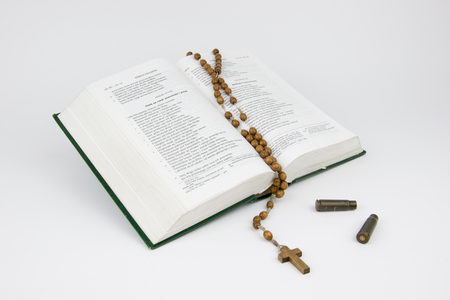 Bible with a rosary and the bullet cartridges Stock Photo - 76626654