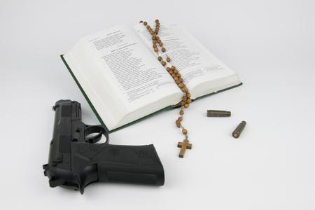 vangelo aperto: Bibbia con un rosario, una pistola e le cartucce di proiettile
