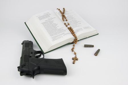 poetic: Bible with a rosary, a gun and the bullet cartridges