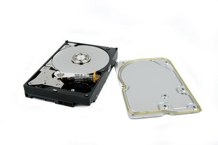 Gedemonteerde harde schijf van PC HDD op de witte achtergrond met platters en hoofdstapel zichtbaar
