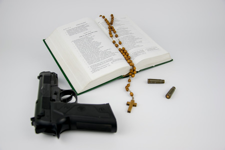 Bible with a rosary, a gun and the bullet cartridges