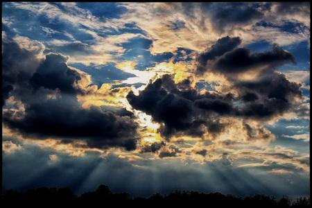sun rays coming through the clouds Фото со стока