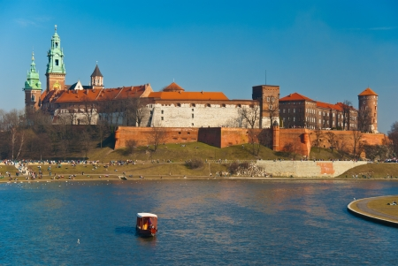 Wawel castle and gondola floating on the Vistula river in Cracow, Poland