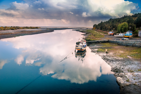 Fishing boat in the reflection of the cloud on the river by the ocean, Aytuy, Chiloe island, Chile, South America