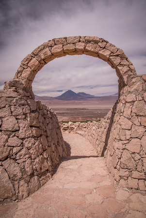 Stone gate at Pukara de Quitor - Inca fortress at Atacama desert with the view at Licancabur volcano in Andes, San Pedro de Atacama, Chile Stock Photo
