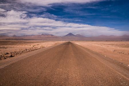 Atacama desert road during desert storm with Andes mountains in the background, San Pedro de Atacama, Chile