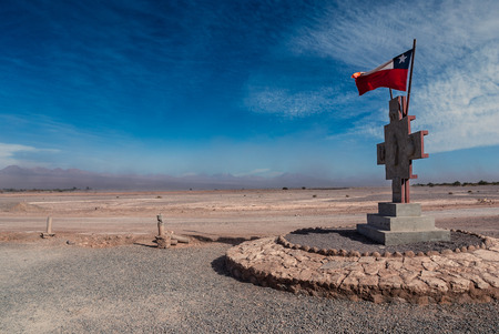Chilean flag and monument in the middle of Atacama desert during desert storm, San Pedro de Atacama, Chile