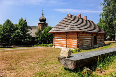Wooden house next to the antique church in historic Polish village, Lesser Poland, Poland