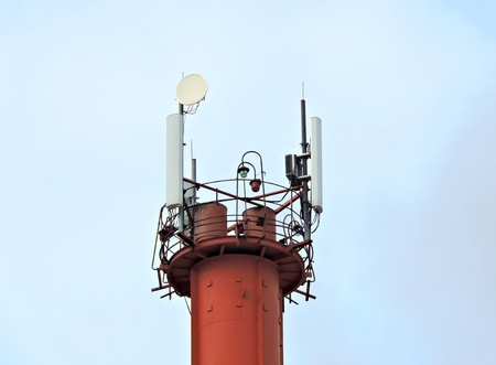 Mobile phone communication radio tower with microwave antenna, celullar transmitter, clouds and blue sky 1