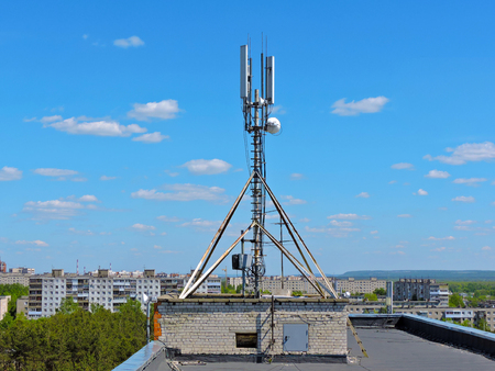 Cell phone antenna on the roof, transmitter. Telecom radio mobile antenna against blue sky 1 Stock Photo