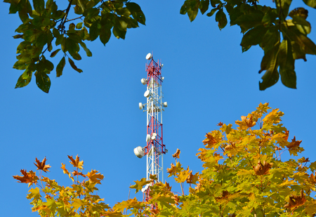 Mobile phone communication radio tv tower, mast with cell microwave antennas and broadcasting network frequency transmitter against the blue sky and trees 1 Imagens