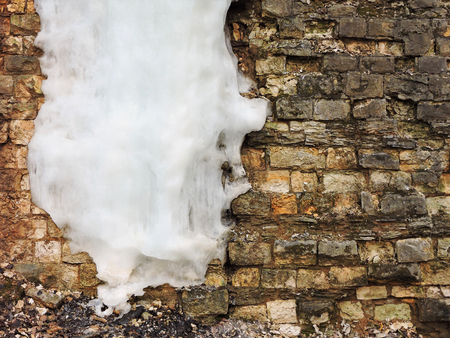 Background old brick wall with big icicle, texture. Vintage