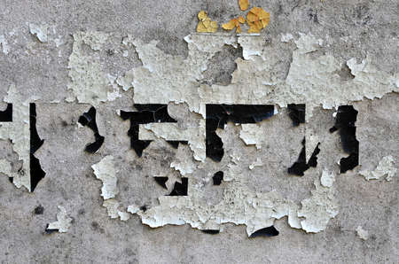 White black grey wall, floor with cracks and remains of pasted paper with unknown text, texture background