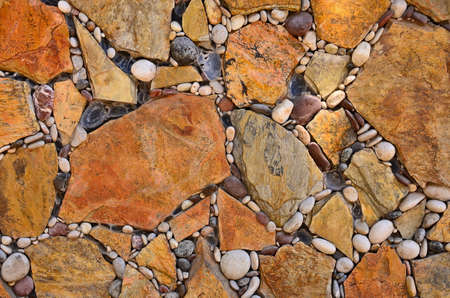 Floor, wall of brown and beige stones laid in a geometric pattern, floor with cracks