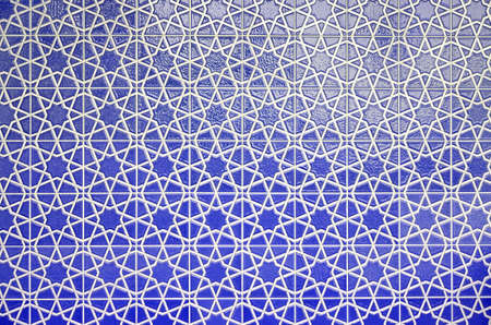Wall of blue tiles with white pattern, drawing of white intersecting lines on the floor, decoration of the house