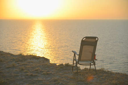 A lone tourist chair with a mug tea, coffee stands on the edge of a cliff against the sky, sea, ocean at sunset.