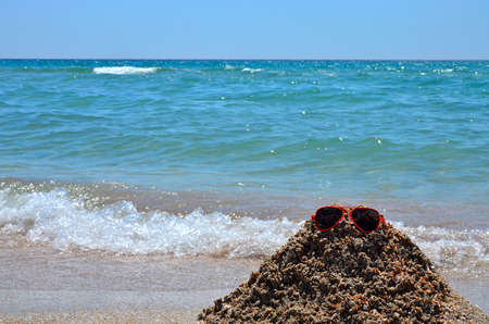 Big waves on the beach, ocean. Red and orange sunglasses lying on a sand slide built by a child on the beach.