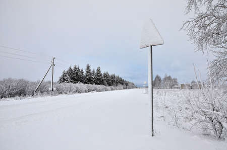 Winter forest road covered with snow. Road sign standing in a snowdrift. Snowfall
