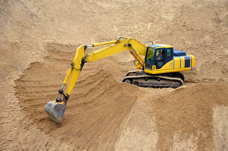 Yellow excavator levels its bucket of sand, earth, clay. Construction of a sand embankment Stok Fotoğraf