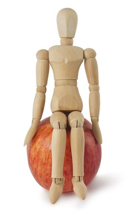 wooden mannequin: The wooden mannequin sits on a ripe apple isolated on white background