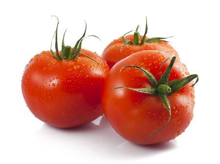 Tres tomates maduros con gotas de agua