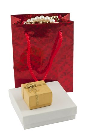 Red giftbag with jewelry and two boxes isolated on white photo