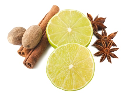 Lime, cinnamon, anis and nutmegs on white background photo