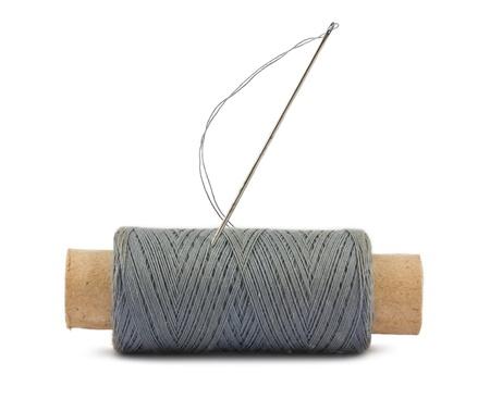 bobina de hilo y aguja aislado en un fondo blanco