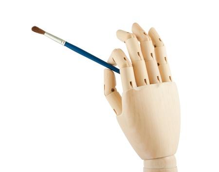 Wooden hand holding brush isolated on white background photo