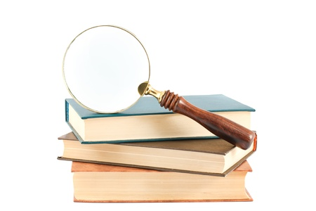Magnifying glass and books isolated on white background photo