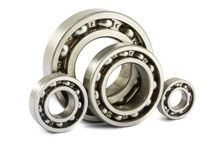 Quatre roulements à billes en acier isolé sur un fond blanc