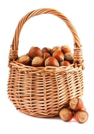 willow fruit basket: Wicker basket with hazelnuts isolated on a white background  Stock Photo