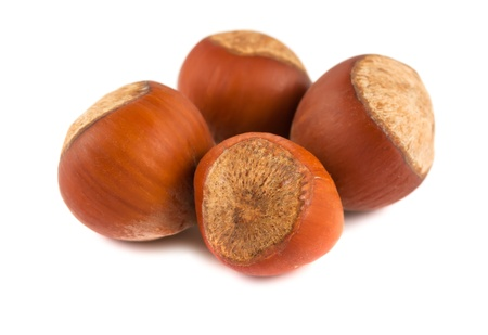 unbroken: Four ripe brown hazelnuts isolated on white background