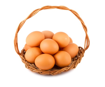 Group of brown chicken eggs on wicker basket isolated over white background photo
